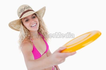 smiling teenager in beachwear playing frisbee