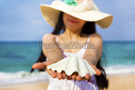 smiling young woman holding shell on