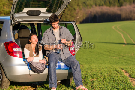camping couple inside car summer sunset