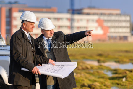 two architects man point at construction
