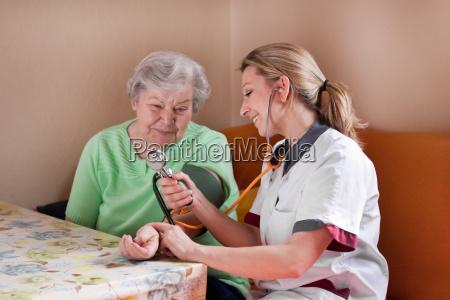 altenpflegerin measures blood pressure at senior