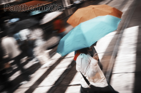 two women under umbrella crossing