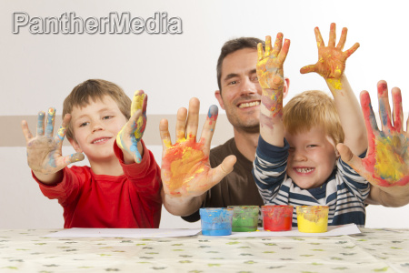 father paints with his children with
