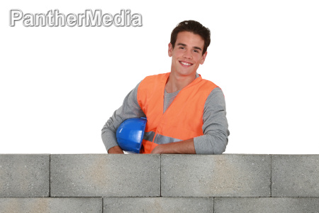 young mason stood by unfinished wall