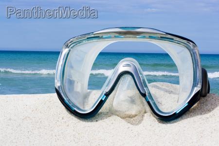 mask on white sand beach
