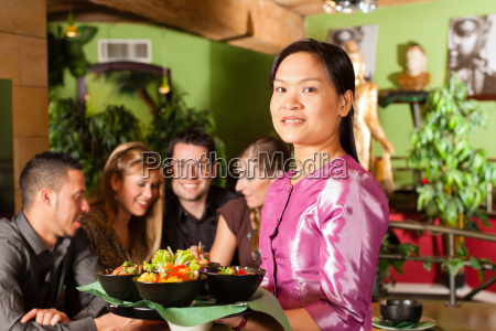young people with waitress eat in