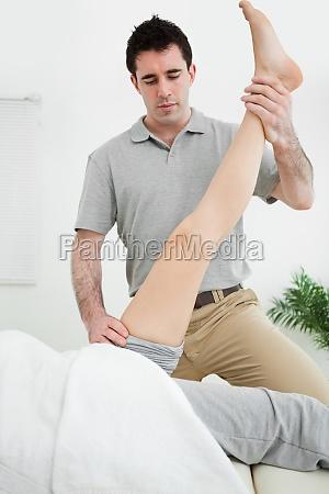 physiotherapist raising the leg of a