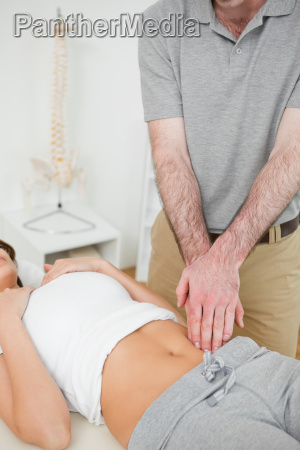 doctor examining the painful abdomen of