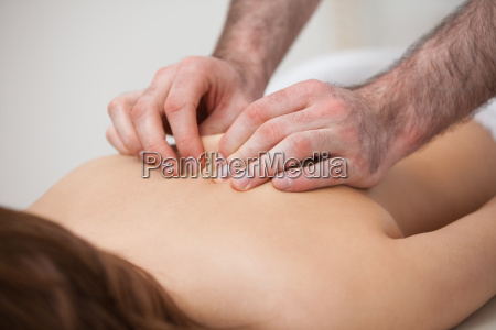 chiropractor massaging his patient while using