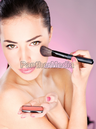 woman applying cosmetic powder brush