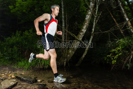 jogger traverses streambed