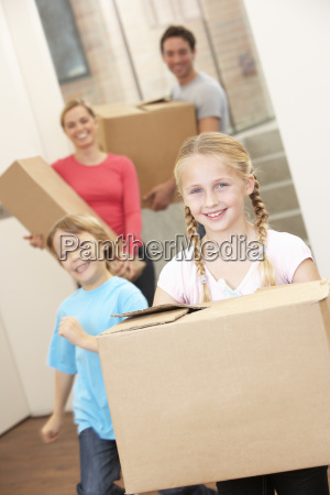family happy on moving day carrying