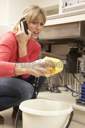 woman mopping up leaking sink on