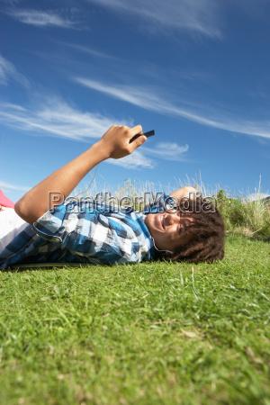 teenage boy lying on grass with