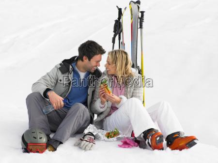young couple with picnic on ski