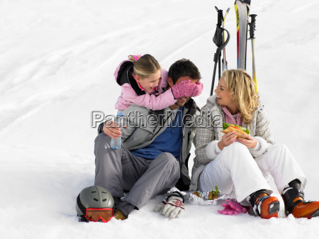 young family with picnic on ski