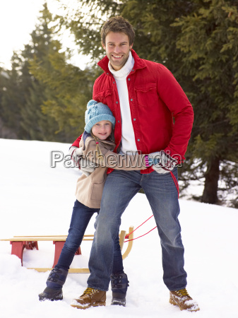 young father and daughter in snow