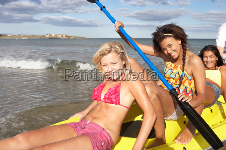teenage girls in sea with canoe