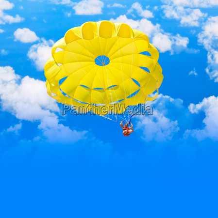 female parachutist over blue summer sky