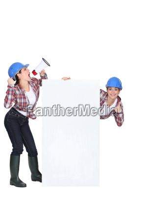 female builder with poster and megaphone