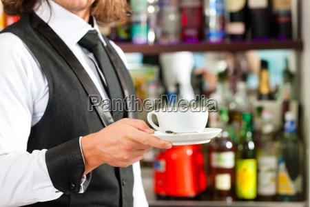 barista prepares cappuccino in his cafe