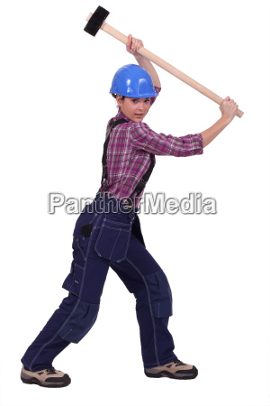 young woman laborer using hammer isolated