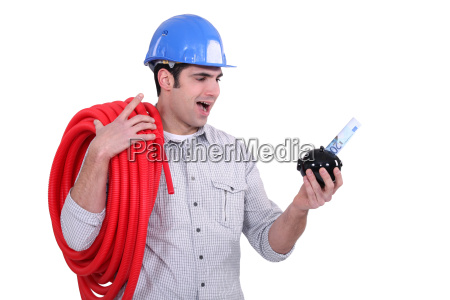 electrician holding piggy bank