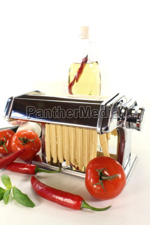 tagliatelle in a pasta machine with
