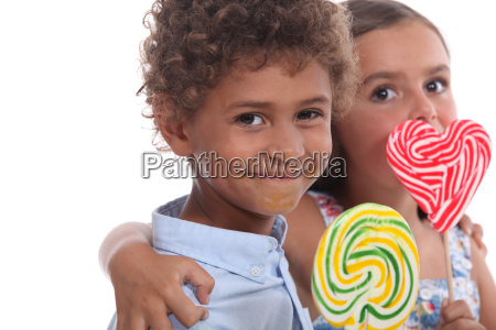 two young children eating lollipops
