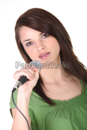 girl singing into microphone on white