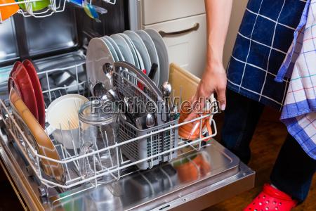 housewife washing dishes with dishwasher