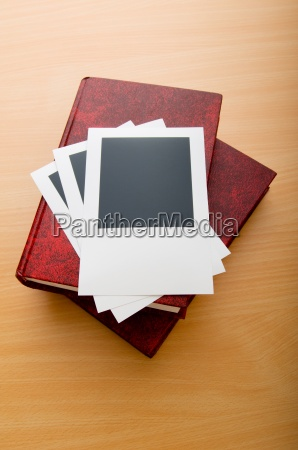 books and blank photos on wooden