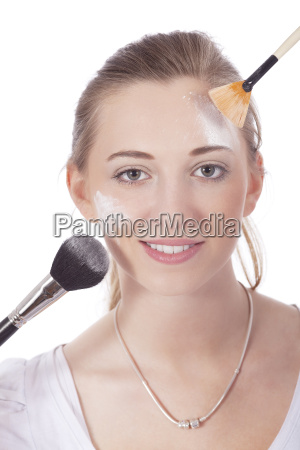 beautiful young woman applying makeup with