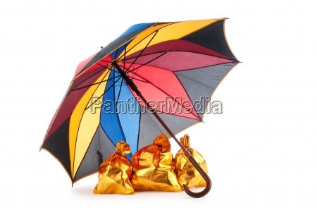 golden sacks under protection of umbrella