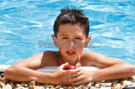 boy eating fruit in swimming pool