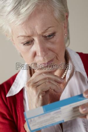senior woman looking at prescription drug