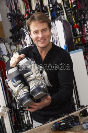 sales assistant with ski boots in