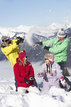 teenage family having snow fight in