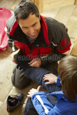 father helping son to put on