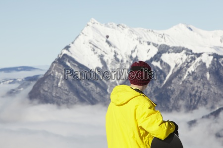 teenage snowboarder admiring mountain view whilst