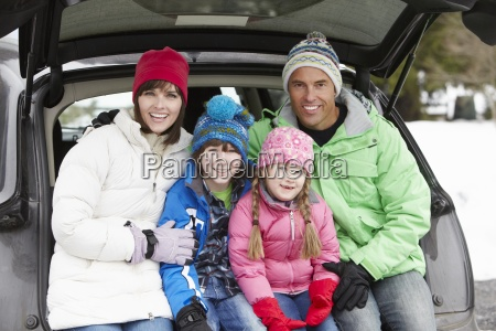family sitting in boot of car