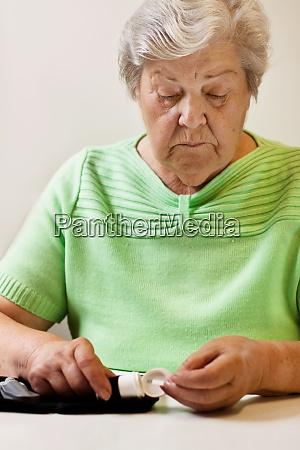 senior woman takes test strips for