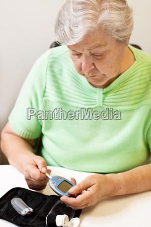 senior woman pushes test strip into