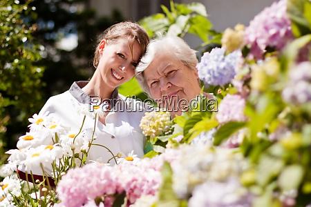 geriatric nurse senior in the garden