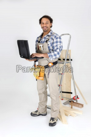 carpenter stood by ladder with laptop