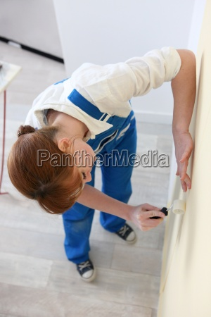 woman smoothing a wallpaper seam
