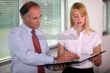 assistant presenting boss with document that