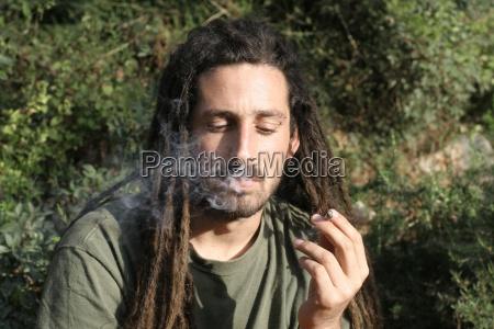 hippy preparing rolling and smoking marijuana