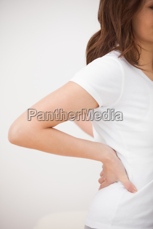woman massaging her painful back in