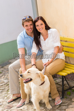 happy couple with dog sitting yellow